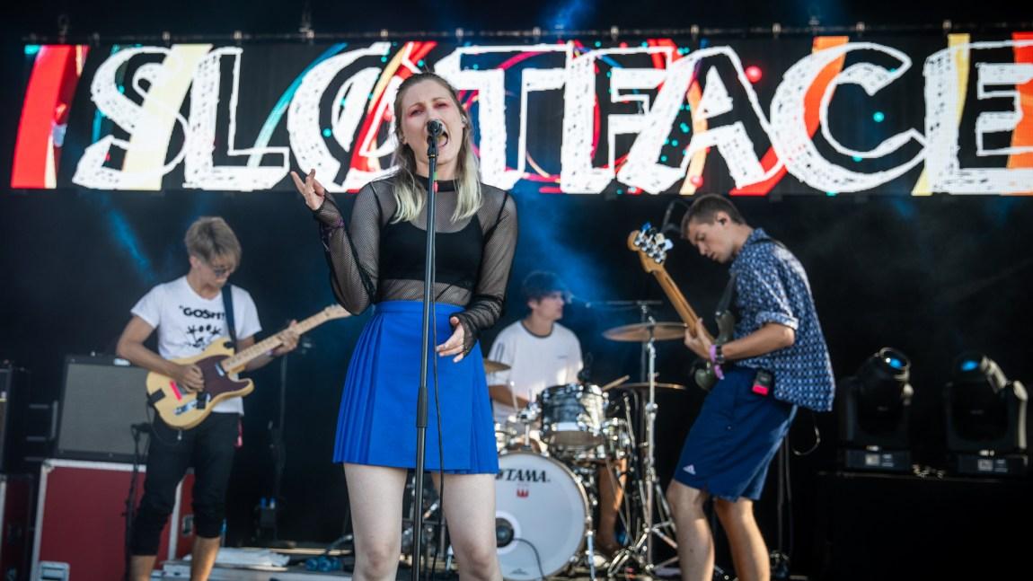 Bandet spiller på scenen. Vokalister står fremst i punkete klær og synger. Bak henne står to gitarister og en trommis. Navnet på bandet står på veggen bak.