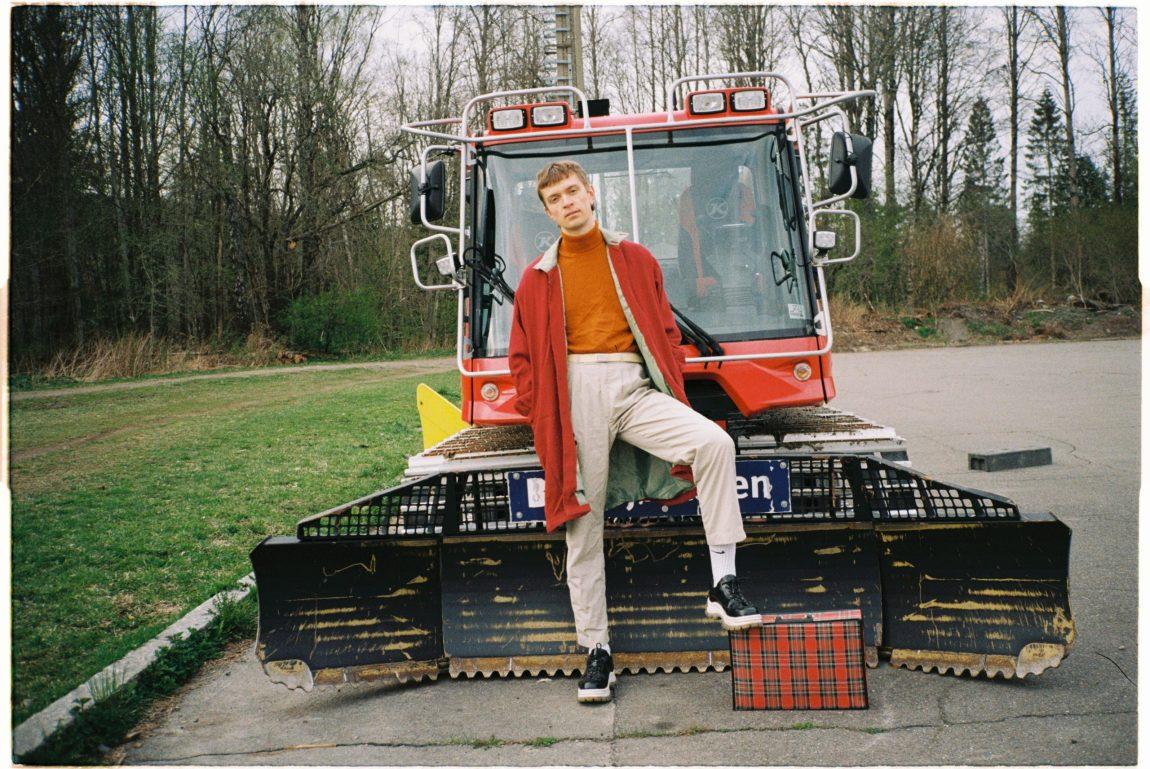 Et bilde av musikeren Lasse Lokøy. Han står foran en måkebil.