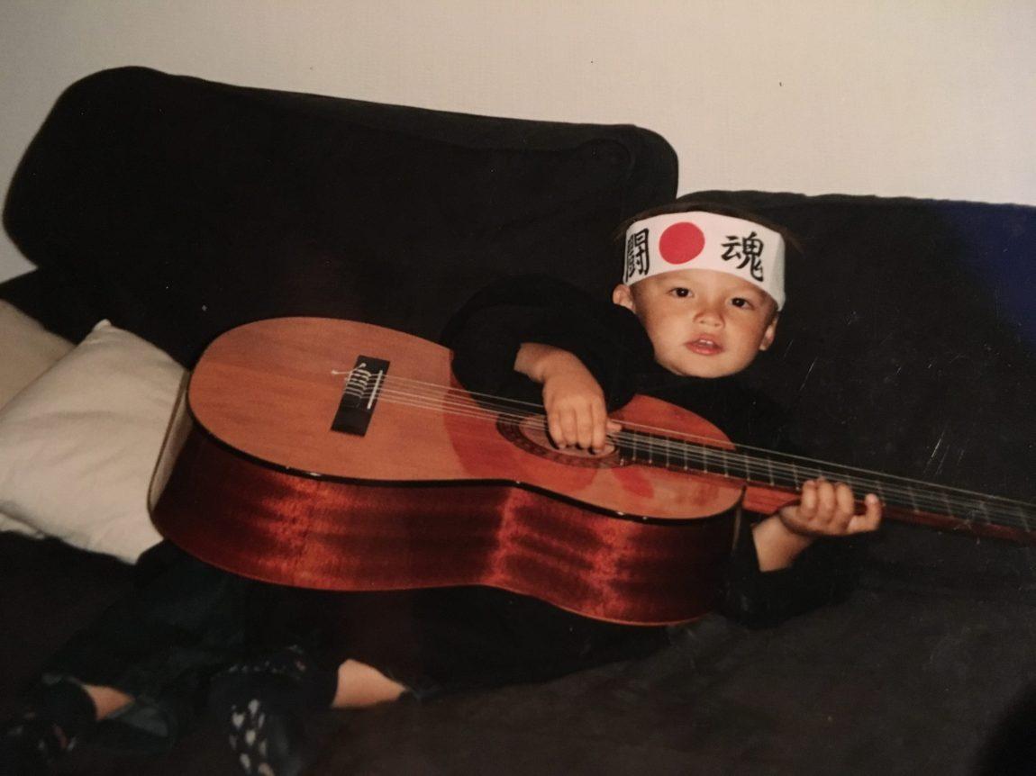 Noah er rundt 5 år gammel. Han ligger i sofaen, med en stor gitar som nesten dekker hele kroppen hans. Han har et panneband med kinesiske tegn på hodet.