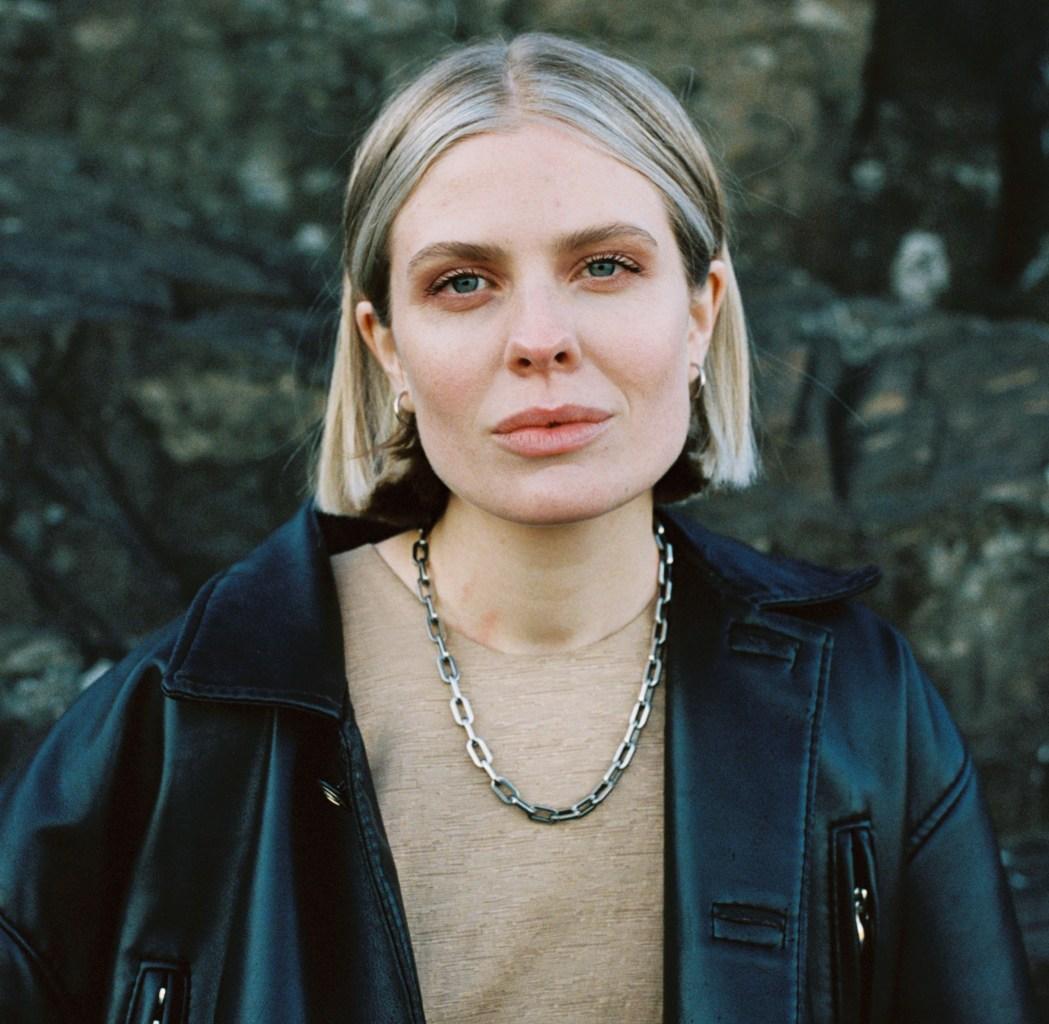 Vokalist i Ponette, Helene Svaland Johansen er kledd i svart jakke og ser i kamera. Ho har kort blondt hår og eit tjukk kjede rundt halsen.