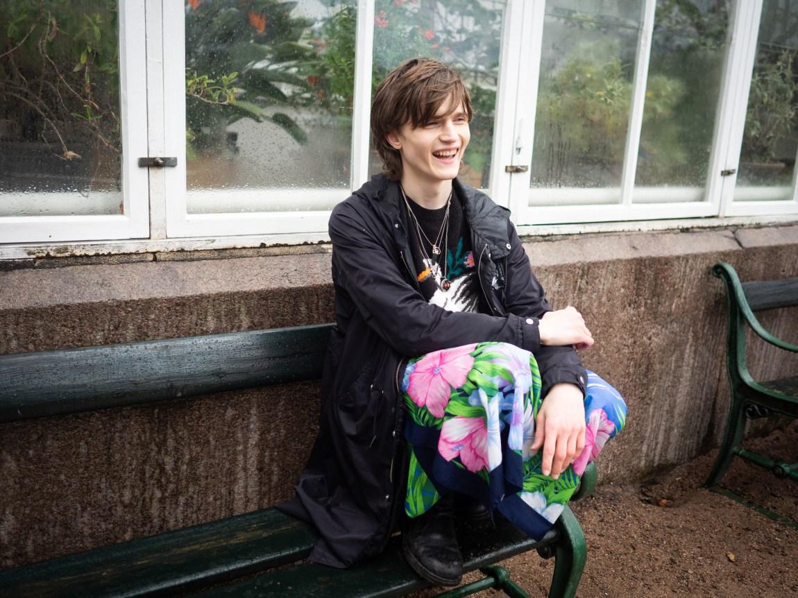 Et bilde av Simon som sitter på en benk utenfor et drivhus og ler