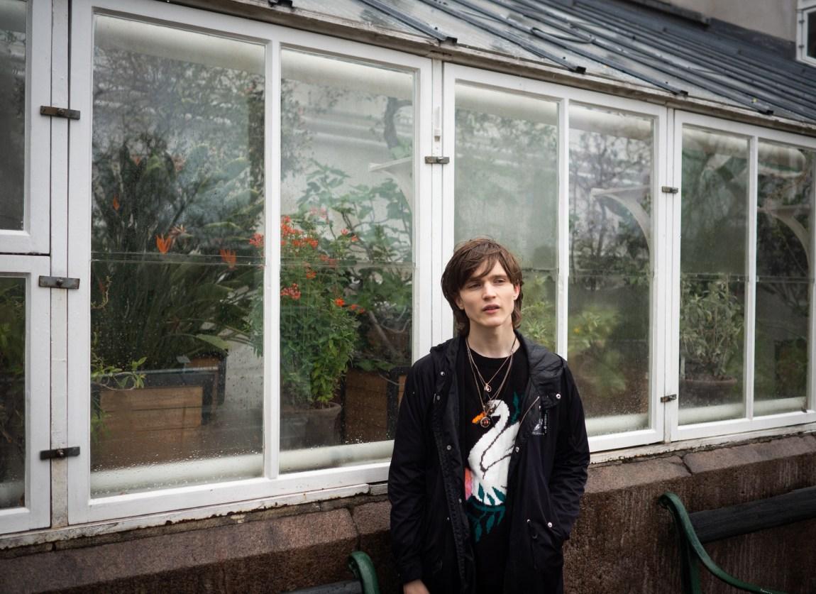 Et bilde av Simon som står i regnet foran et drivhus. Han ser ettertenksomt til siden