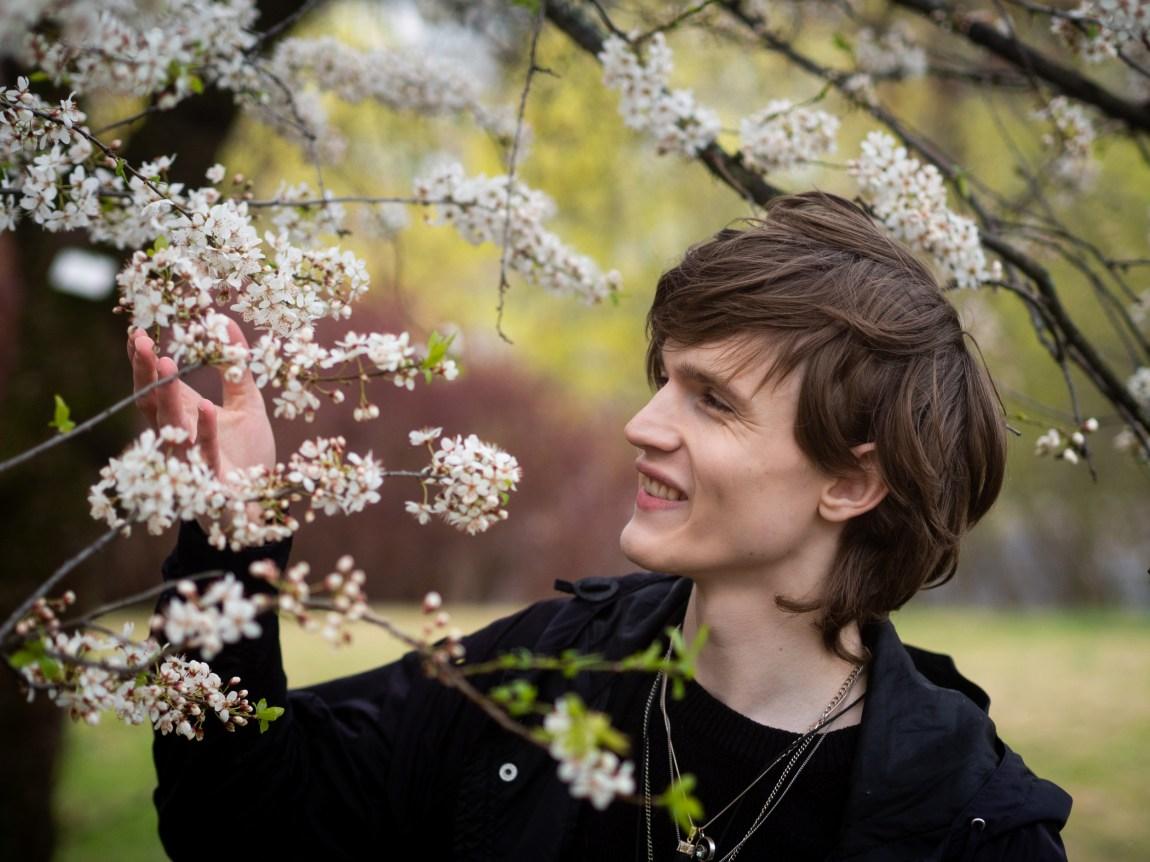 Et bilde av Simon som inspiserer blomstene på et tre i Botanisk hage på Tøyen mens han smiler