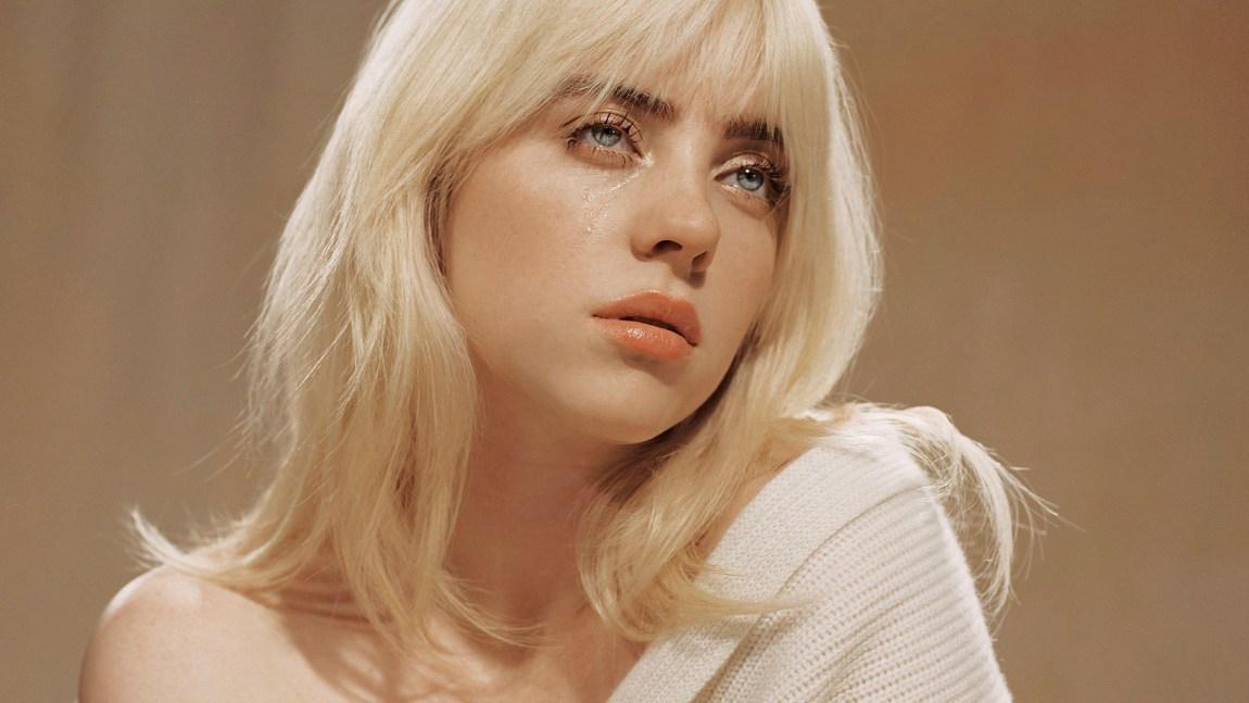 Et bilde av Billie Eilish som ser drømmende ut i luften (til siden) mens én tåre renner ut av øyet hennes. Bilde er det samme som på platecoveret til Happier than ever.