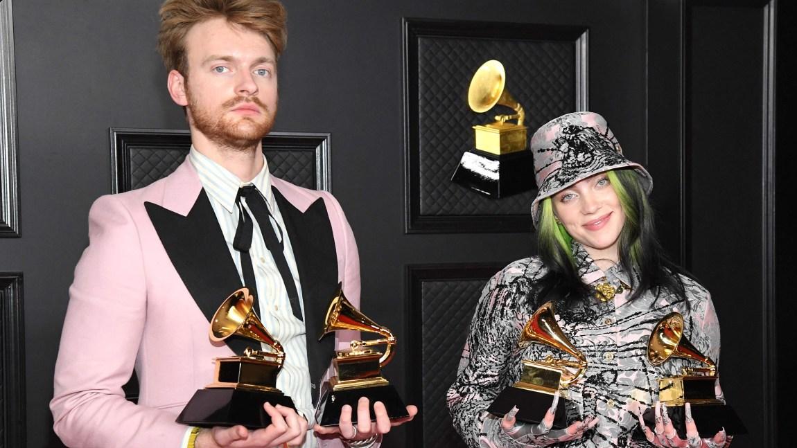 Et bilde av Finneas og Billie Eilish. Finneas ser alvorlig ut, men Billie smiler. De holder Grammy-statuetter. Bak dem ser man en vegg med Grammy-logoen.