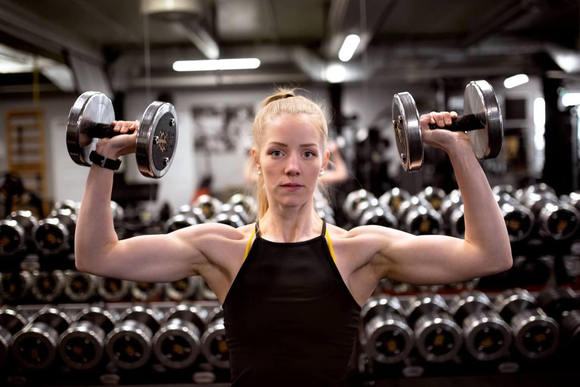 Tonje er på treningssenter og kikker inn i kameraet. Hun løfter to vekter og flekser musklene.
