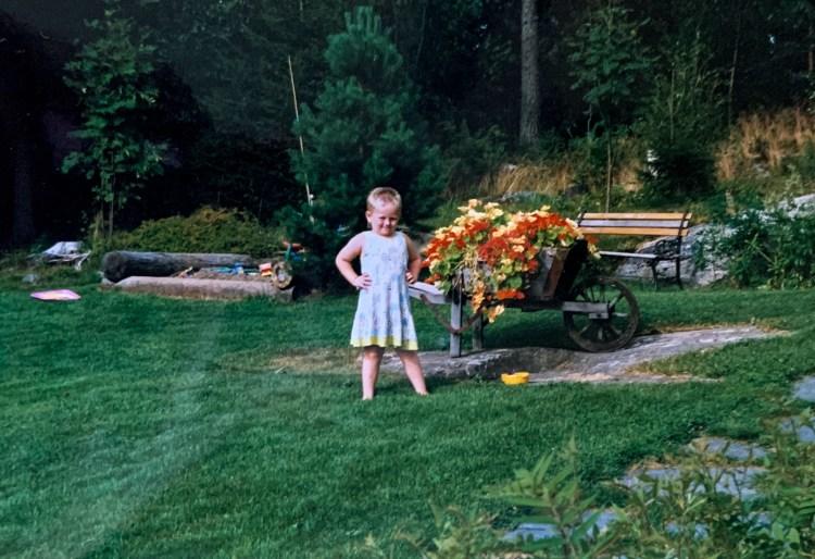 Barndomsbilde tatt med analogt kamera. Sondre står midt i bildet ved siden av gule og røde blomster. Han har hendene i sida, og smiler. På seg er en grønn-blå kjole med gule og hvite blomster. Alt rundt han er grønt.
