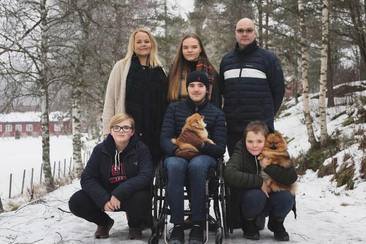 Familien på seks står oppstilt, medan dei smiler til kamera. Marcus og vetlebroren held kvar sin pomeranian. Det er eit tynt lag med snø på bakken.