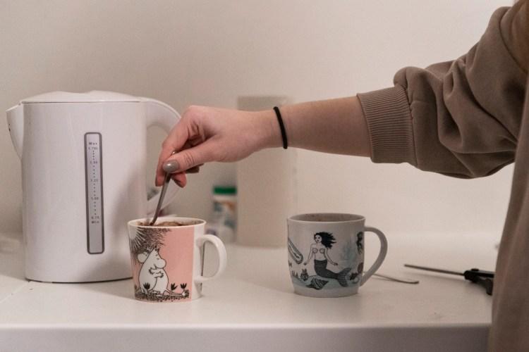 På kjøkkenbenken står en hvit vannkoker til venstre. I midten står sto kopper med kakao: Til venstre en rosa Mummi-kopp og til høyre en hvit kopp med havfrue og blå havmotiver. Armen til Synne beveger seg over koppene og rører med en teskje i Mummi-koppen.