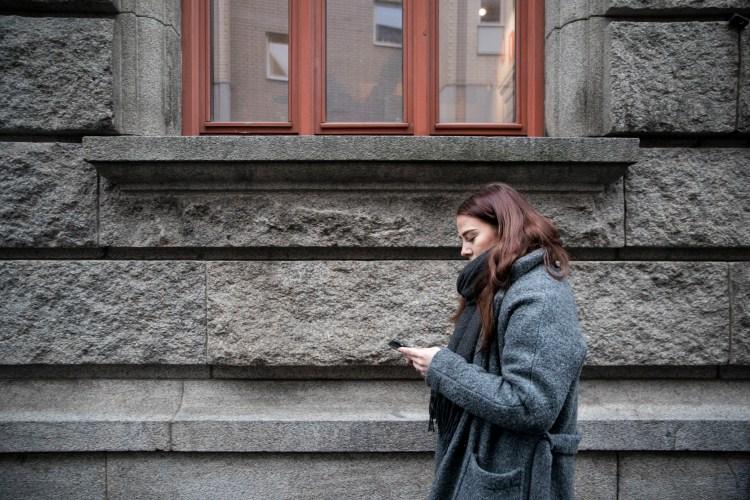 Synne er plassert til høyre i bildet, foran en stor grå, murbygning med store steiner. Hun matcher bygget med den grå kåpa og titter ned i telefonen mens hun går bortover veien. Over henne er det tre vinduer med rød vinduskarm, som matcher det gyldne håret.