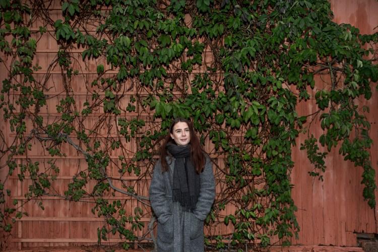 Synne ser opp, og det halvlange gyldenbrune håret ligger foran skuldrene, samtidig som det blåser litt med vinden. På seg har hun et mørkegrått skjerf og en lysegrå ullkåpe. Bak henne er en rødoransje vegg med en klatreplante bestående av grønne blader.
