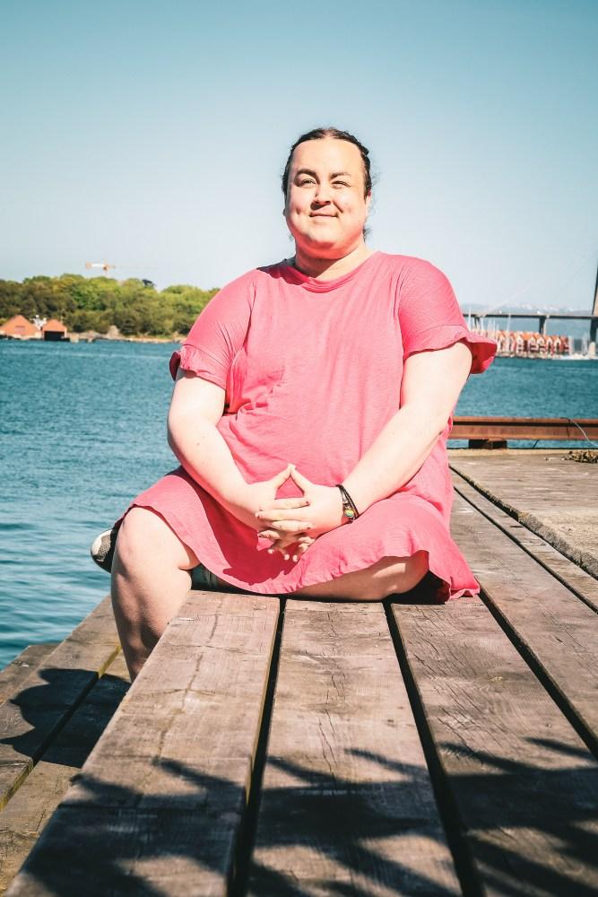 Karoline smiler lurt. Hun sitter på en brygge, med beina i kryss, iført en rosa sommerkjole, og stirrer ut i luften. Været er idyllisk og i bakgrunn ser vi en tydelig blåfarget fjord.