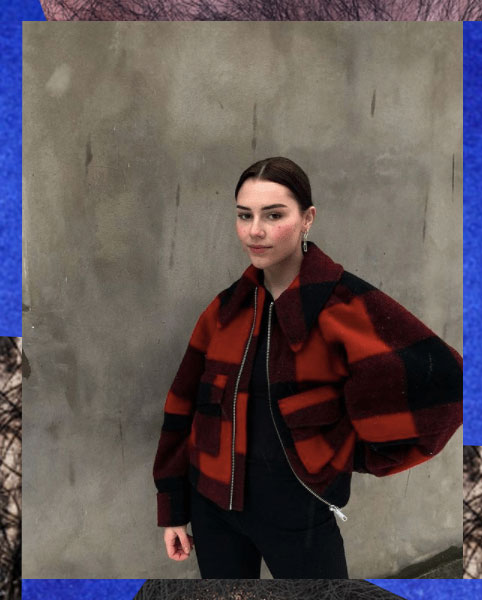 Ung kvinne med alvorlig blikk ser i kamera. Hun har hånda på hofta og er ikledd en rød jakke med ruter.
