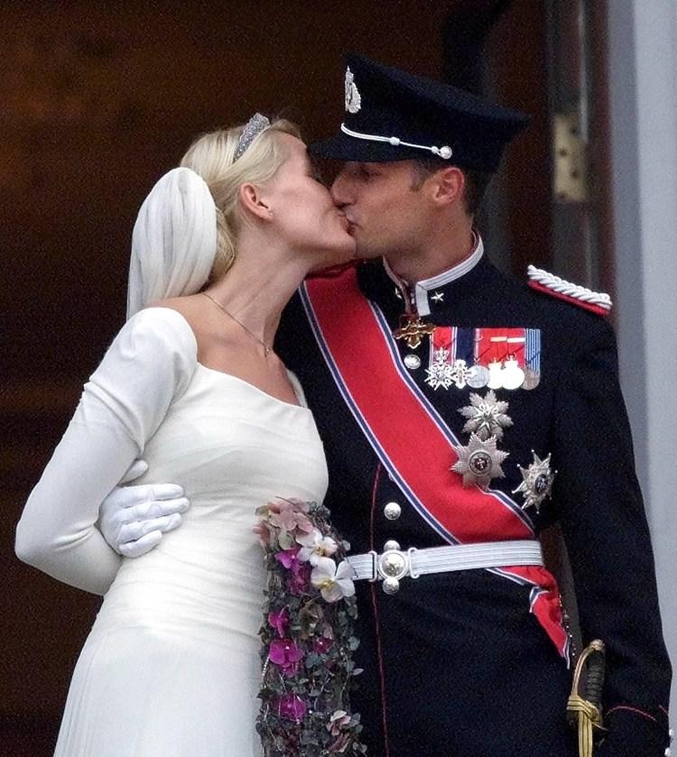 Brullypsbilete av Mette-Marit og Håkon som kysser på balkongen. Ho har kvit brudekjole med djup hals og ermer. Ho held armen bak ryggen, har tiara i håret og slør. Håkon held rundt ho, og dei kysser. Han har på seg uniform med fleire medaljar, hatt og eit raudt band som går over skuldra.