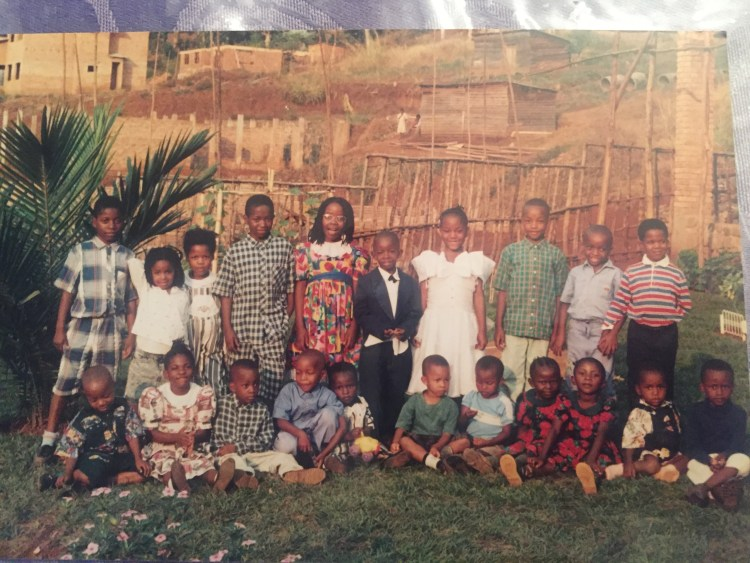 Oppstilt bilde av Mush saman med 20 søskenbarn på omtrent same alder. Mush står i midten med den litt for store dressen. Alle barna har festklede på og smiler fint til kamera.