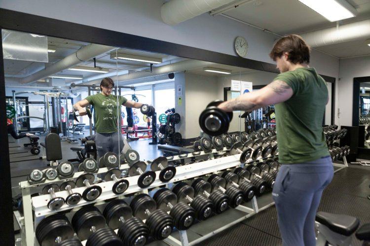 Sebastian løfter vekter framfor speglet. Han har på seg joggebukse og grøn t-skjorte. Han ser konsentrert inn i spegelen.