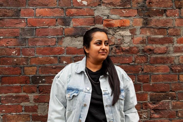 Kiran Anwar står foran en murvegg. Hun har dongerijakke på og står og ser ut mot siden med en alvorlig mine.