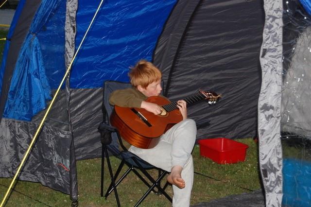 Bjarte sitter krøket over gitaren i en fluktstol under en blå teltduk. Han er på tur, men gitaren er med. Han har lagt venstre fot over høyre lår og lagt gitaren i fanget. Han ser ned på strengene mens han spiller. Han er barfot, men har joggebukse og genser på.