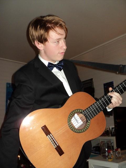 En ung Bjarte står i svart dress og hvit skjorte med sløyfe i halsen. Han har gitaren på magen og har nettopp spilt eller skal til og spille. Det kan se ut som han er hjemme i stua i Sandviken, og deltar i selskap. Han ser ut mot siden og har venstre hånd i et grep over strengene på gitaren.