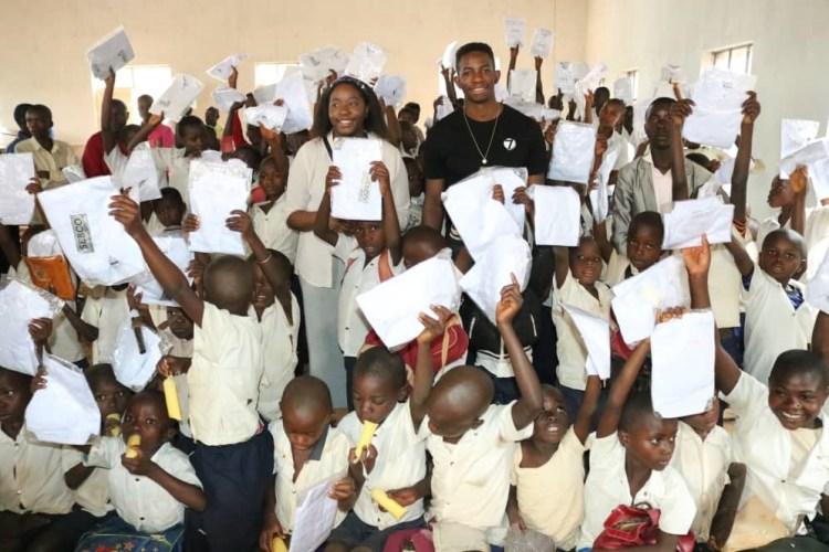 Mush og systera Neema står i eit klasserom fullt av barn som held opp heilt nye, kvite skuleskjorter.