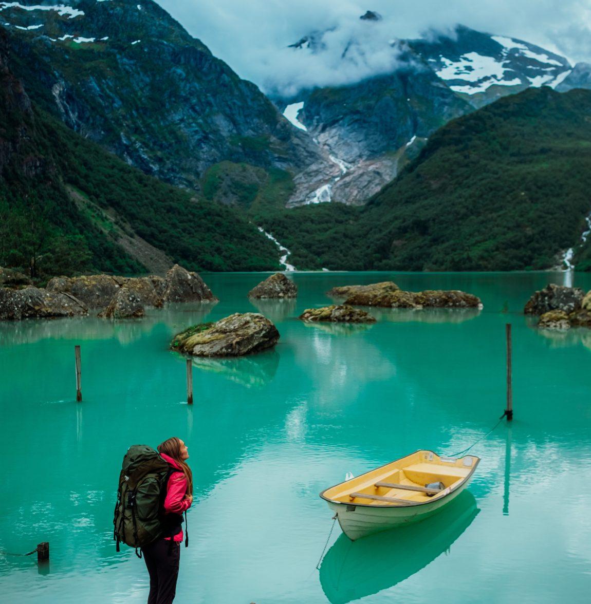 Her ser vi Helene stående ved Bondhusvatnet. Dette er en innsjø godt kjent for sine svært grønne fargetone. Men selv om dette var destinasjonen, stirrer Helene heller opp mot de høye fjelltoppene som omkranser det lille vannet.