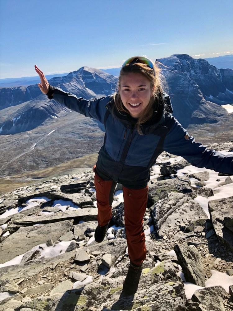 På en ukjent fjelltopp står DNT representanten og balanserer på en fot, med hendene ut i vinger. Bildet er tatt i helprofil og Josephine smiler bredt rett i kameraet.
