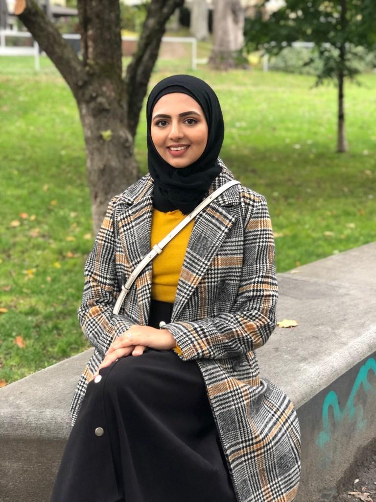 I en park sitter en ung muslimsk dame, Ghilma Salam, med bena i kryss. Hun er iført en grå, stripete jakke, med en gul genser under, svart og posete bukse og en svart hijab. Ghilma smiler bredt, mens hun ser rett i kameraet.