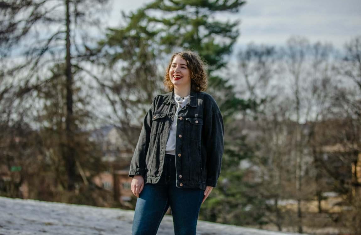 Leona står i ein park. Ho ler og ser ut til sida. Ho har kort, brunt krøllete hår, raud leppestift, blå dongeribukse, grå dongerijakke og ei kvit t-skjorte på seg. Bakken bak ho er dekt av eit tynt lag snø, og bak ho ser ein hus og nokre tre.