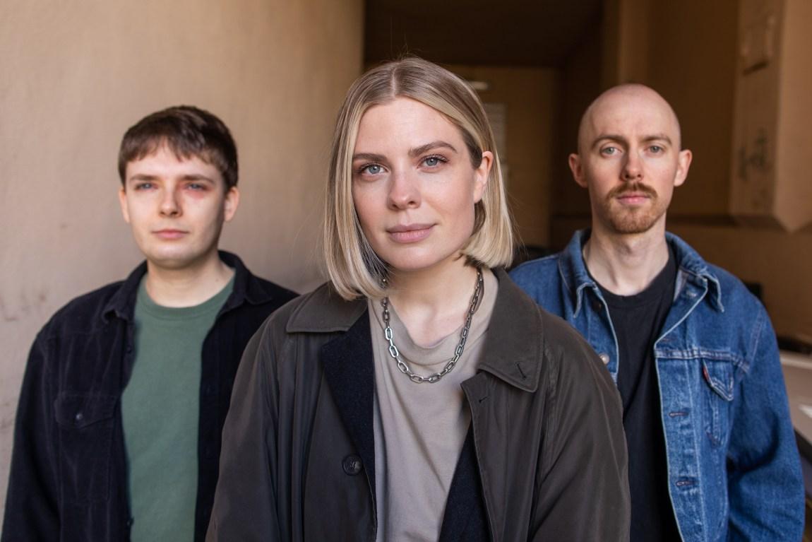 Alle tre banmedlemmene står samlet. Helene står fremst, med Johan og Johannes bak seg. De smiler så vidt til kamera.