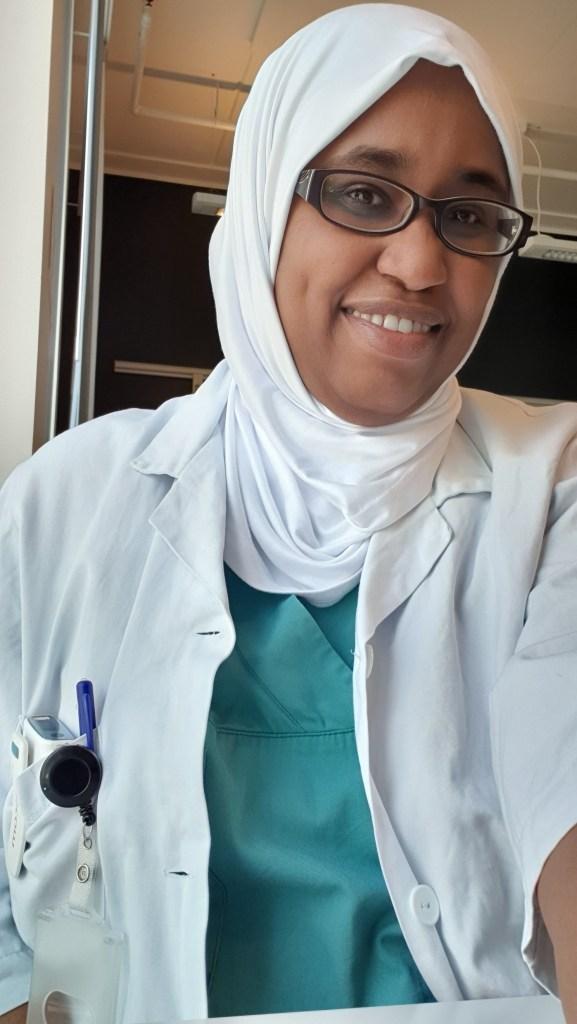 Bilde av lege Samah Abdelkareem som smiler mot kameraet. Hun har legefrakk på med grønne sykehusklær under. Hun har hvit hijab på hodet og briller i ansiktet. I frakken har hun en lomme med en personsøker i og en penn som henger fast i lomma.