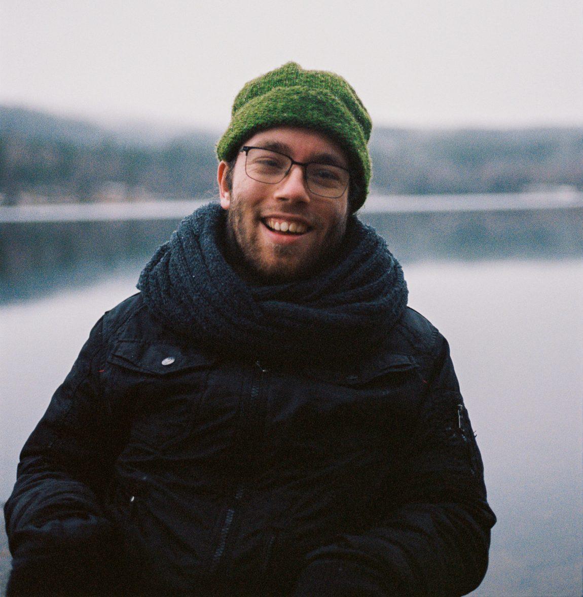 Johannes har på seg en grønn lue og tykt skjerf. Han sitter ved vannkanten til Sognsvann og smiler til kamera.