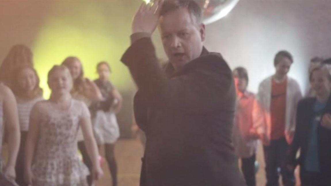 MIssegeneralen dansar i musikkvideo, bak han står masse barn og ser på.