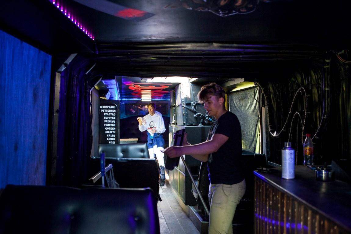 To gutar vaskar inne i ein diskotekliknande buss.