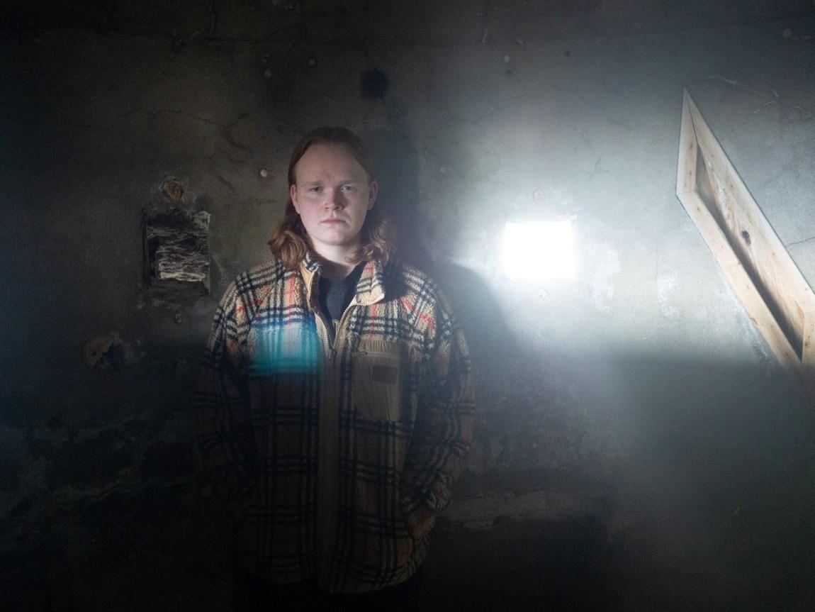Et bilde av Jon Martin som står inni en grotte. Sola skinner inn gjennom små vinduer og treffer hodet hans