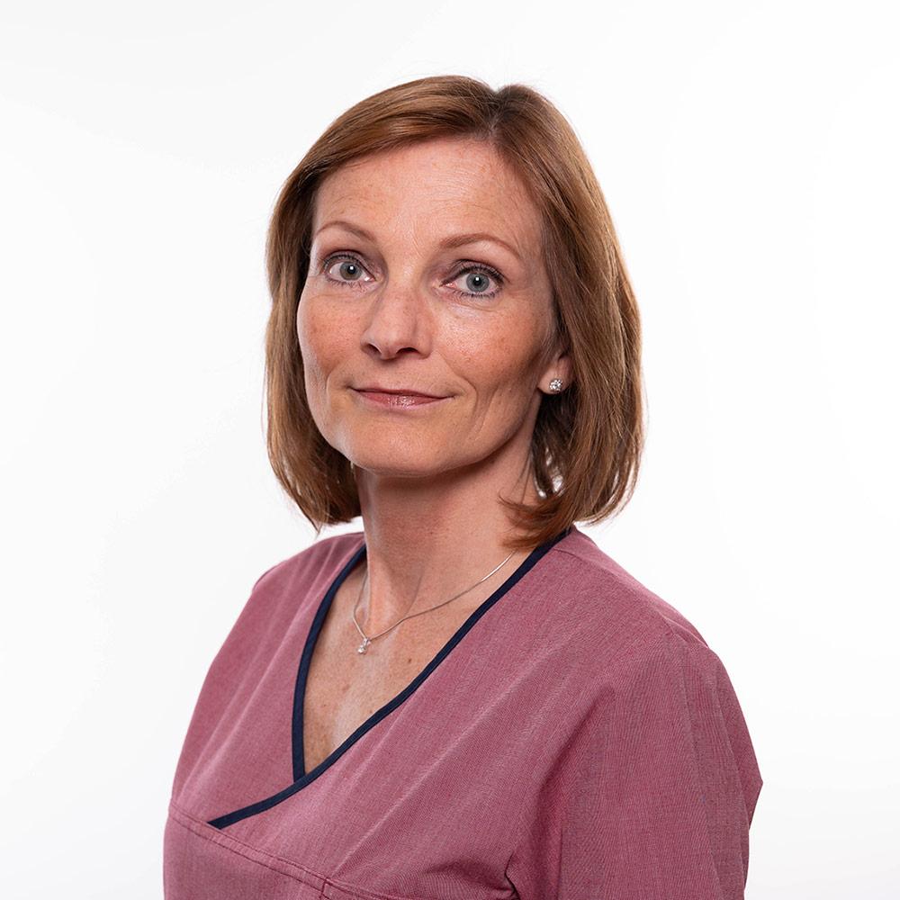 Gynekolog Kristin Offerdal ser rett i kamera. Hun har rosa legeskjorte på og det brune håret hviler på skuldrene. Minen er alvorlig.