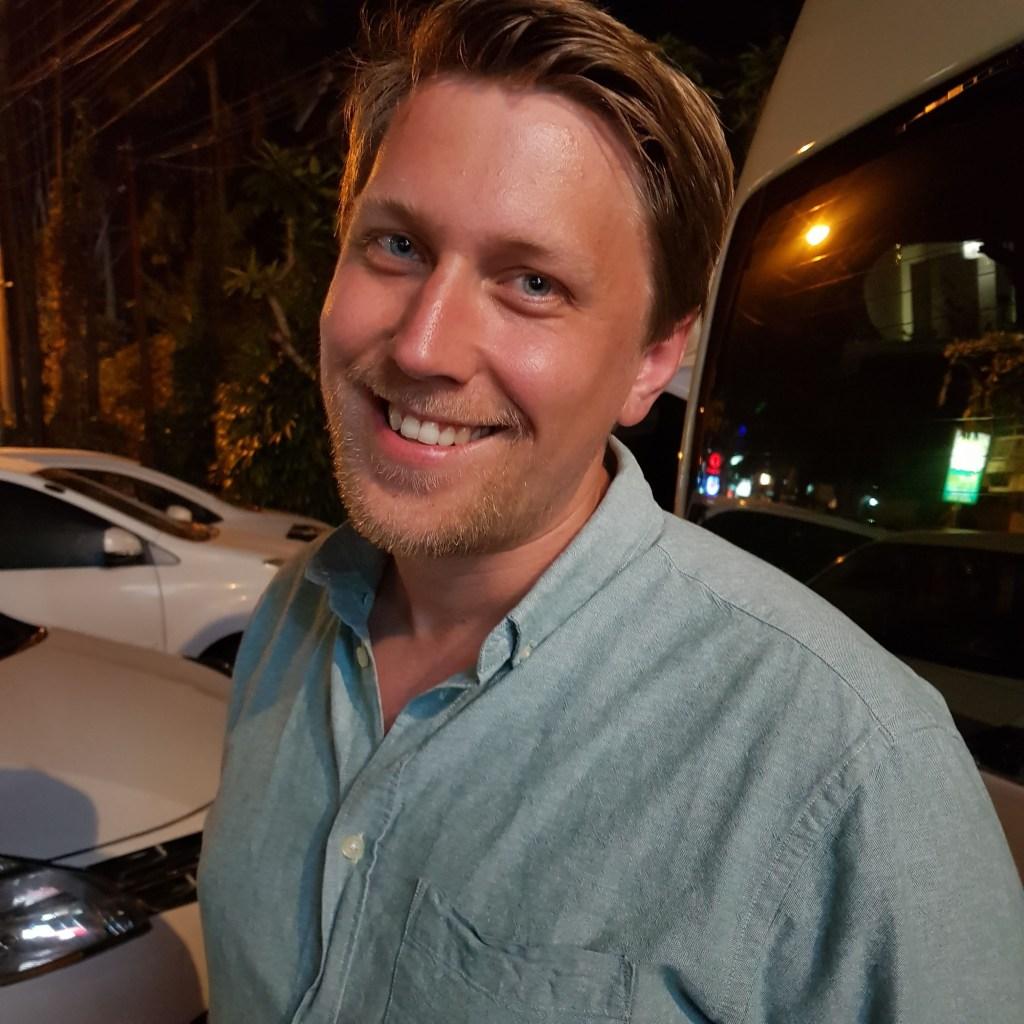 Anders har på seg en lyseblå skjorte som matcher øynene hans. Han smiler inn i kameraet. Det er mørkt ute. Bak han står det flere biler parkert.
