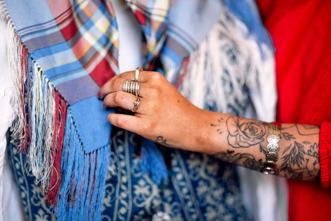 Sara sin tatoverte hånd rører ved hennes fargerike bunadssjal