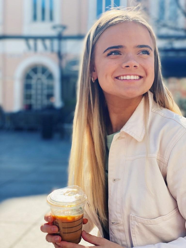 Linnea smiler og ser forbi kameraet. I hånda holder hun en kaffe fra starbucks. Hun har på seg en hvit olajakke og i bakgrunnen får vi se en blury bygning.