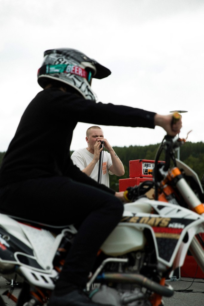 Vokalist Markus Danjord syng medan ein motorsykkel passerer framfor han.