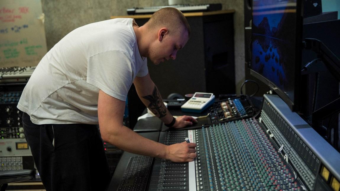 Vokalist og lydteknikar i Lüt, Markus Danjord, står lent over eit miksebord i studio.