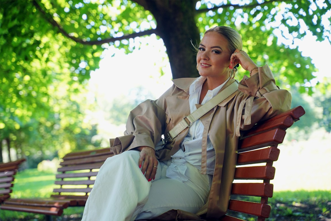Alexandra sitter på en rød benk i en park. Det er sol og grønne trær bak henne, og hun lener hode på handa. Hun har på seg en hvit skjorte og en beige kåpe med en hvit veske hengende over skulderen. Håret et satt opp i en hestehale.