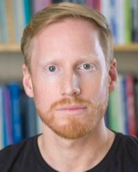 Ein mann med lyseblondt hår og lyseblondt skjegg ser alvorleg inn i kameraet. Han har blå auger og har på seg svart skjorte. Bak han ser vi så vidt ei bokhylle.
