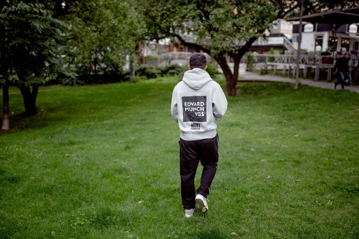 Mert har snudd ryggen til og går gjennom en gresskledd park. På genseren står hans det skrevet «Edvard Munch vgs» i hvite blokkbokstaver.