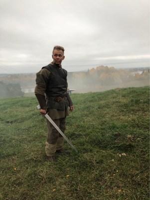 Ola i klærne fra serien Beforeigners. Han har et stort og langt sverd. Og grønne klær med rustning. Bak han er det grønt gress, og litt lengre bak er det skog.