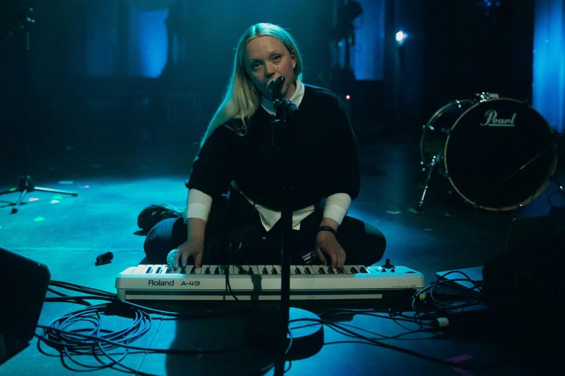Et bilde av Vilde Tuv som sitter på gulvet på scenen og spiller keyboard
