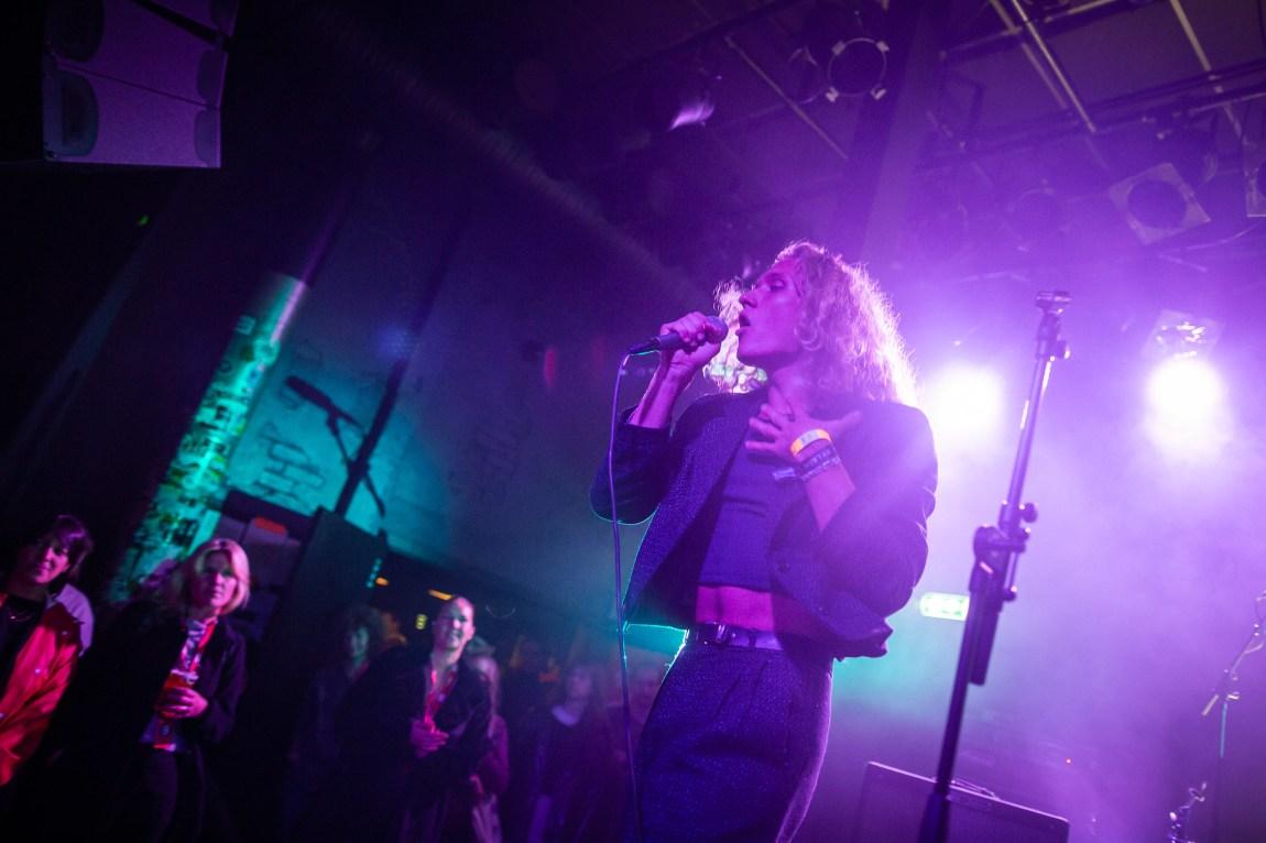 Et bilde av Cham Leon på scenen. Man ser noen publikummere som følger med