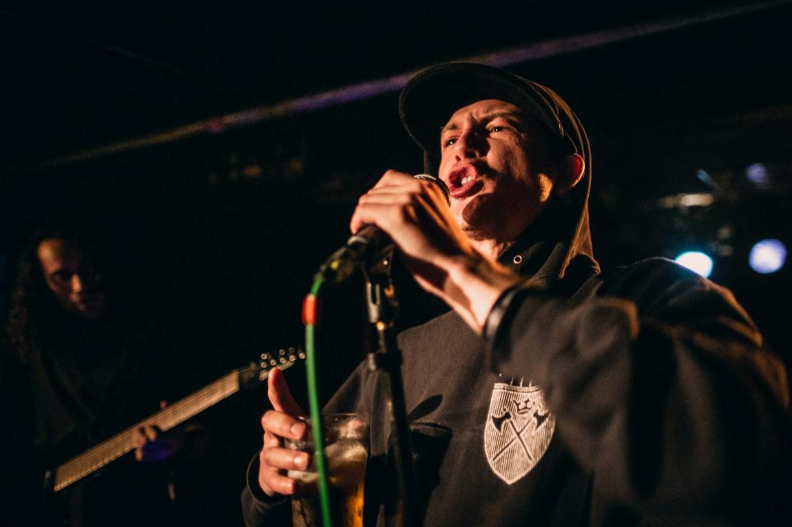 Et bilde av Kobe som holder en øl i hånda mens han synger inn i mikrofonen på scenen