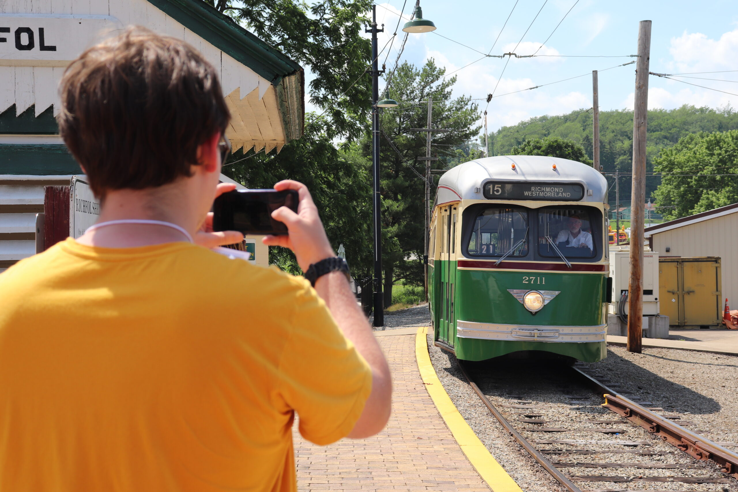 Over the shoulder shot of a man taking a photo with his cell phone of 2711 as it pulls into Richfol lower platform