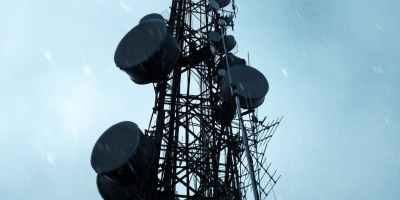 black satellite tower under blue skies