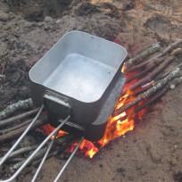 Madlavning i mess tin over dakota fire